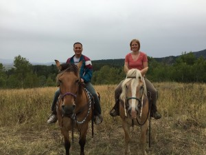 Mark and Lizzy smiling amidst the fresh air while horseback riding with the Rockin' M Ranch in Alpine, WY.